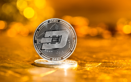 Dash cryptocurrency coin on a golden background Stock Photo