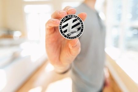 Litecoin cryptocurrency coin held by a man in a bright room 写真素材