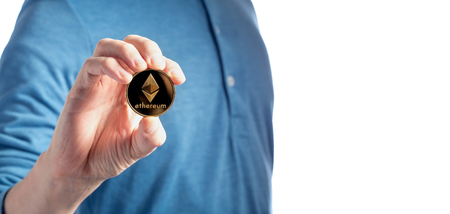 Ethereum cryptocurrency coin held by a man on a white background