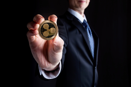 Ripple cryptocurrency coin held out by a man in a suit 写真素材