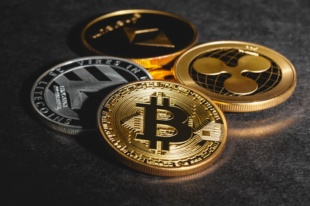 Bitcoin, Litecoin, Ripple and Ethereum coins on a dark background