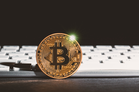 Bitcoin cryptocurrency coin on a dark background with keyboard
