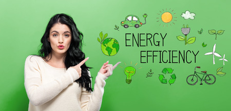 Energy Efficiency with young woman on a green background Archivio Fotografico