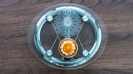 Modern glass and steel scale with a small pastry dieting theme