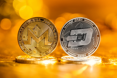 Monero and Dash cryptocurrency coins on a golden background Stock Photo