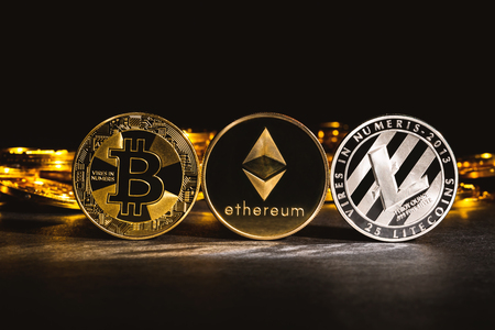 Bitcoin, Litecoin and Ethereum coins on a dark background Фото со стока