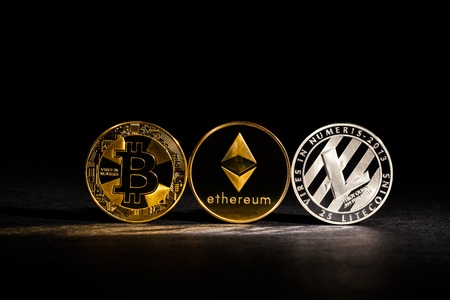 Bitcoin, Litecoin and Ethereum coins on a dark background Stock Photo