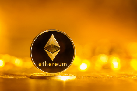 Ethereum ether coin on a shiny golden background Stock Photo