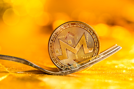 Monero cryptocurrency fork concept on a golden background Stock Photo