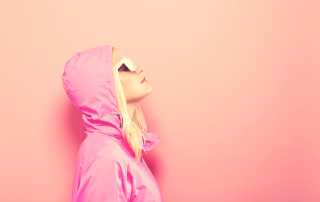 Fashionable woman in pink raincoat and sunglasses on a pink background