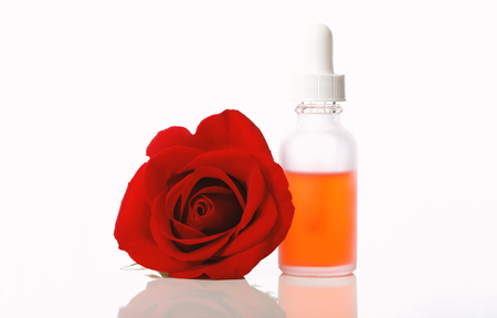Dropper bottle with rose bloom isolated on a white background