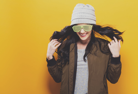 Fashionable and happy woman in a bomber jacket on a golden yellow background Stockfoto
