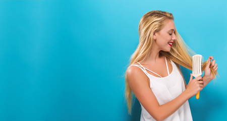 Beautiful woman holding a hairbrush on solid background Foto de archivo - 100907070