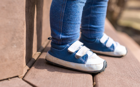 Toddler boy wearing his blue sneakers outside