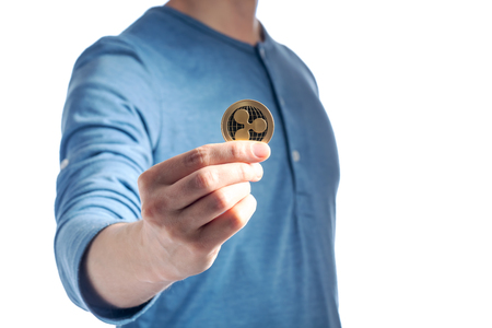 Ripple XMR cryptocurrency coin held by a man on a white background