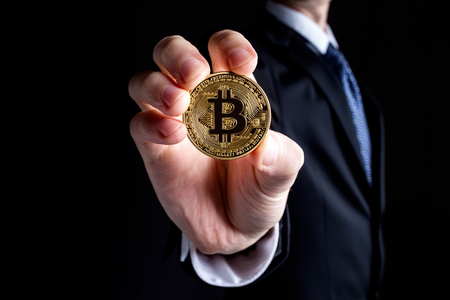 Bitcoin cryptocurrency coin held out by a man in a suit