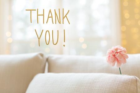 Messaggio di ringraziamento con un fiore in un divano interno luminoso