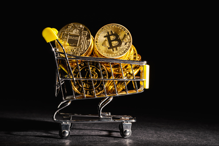 Bitcoin cryptocurrency coins with shopping cart consumer spending theme Stock Photo