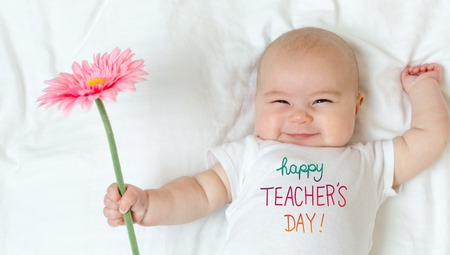 Teachers Day message with baby girl holding a flower Stock Photo