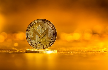 Monero cryptocurrency coin on a golden background
