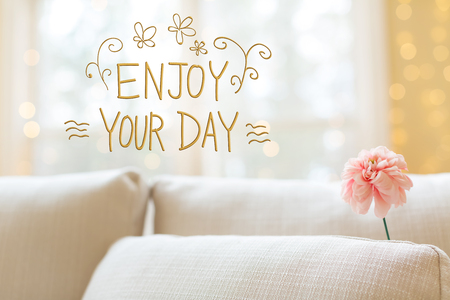 Enjoy Your Day message with a flower in a bright interior room sofa Stock Photo