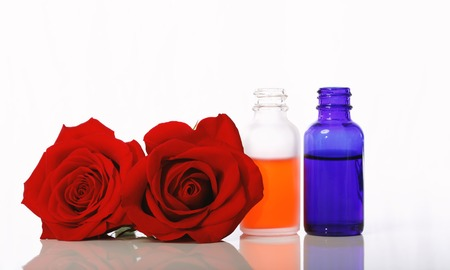 Dropper bottles with roses isolated on a white background
