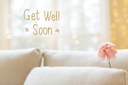 Get Well message with a flower in a bright interior room sofa Stockfoto - 101736559