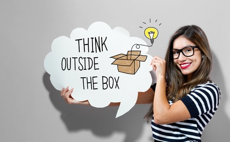 Think Outside The Box text with young woman holding a speech bubble