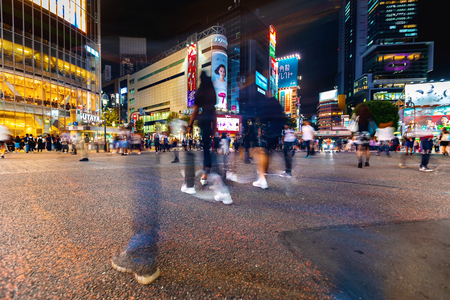 TOKYO, JAPAN - SEPTEMBER 25, 2017: People cross the Shibuya Scramble crosswalk, one of the busiest intersections in the world. Stock Photo - 118177825
