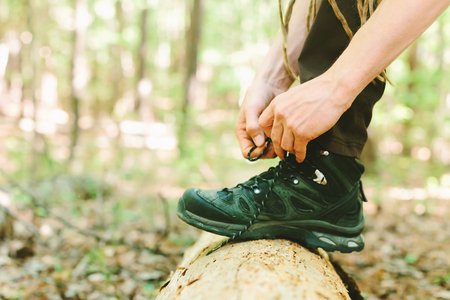Hiker tying boot laces on a log in the forest Zdjęcie Seryjne