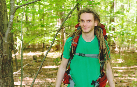 Happy male hiker with backpack trekking through the forest