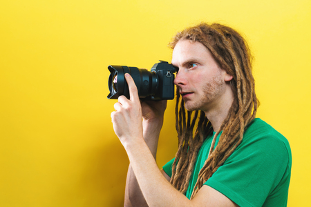 Young man holding a professional camera on a yellow background 写真素材