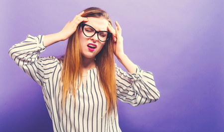 Young woman feeling stressed on a solid background Foto de archivo - 102480924