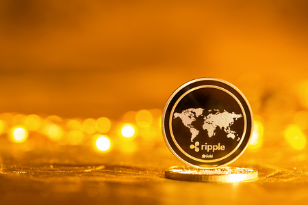 Ripple cryptocurrency coin on a bright gold background 版權商用圖片