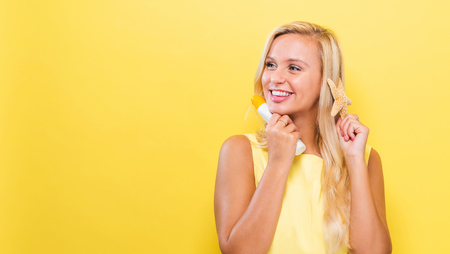 Young woman a bottle of sunblock on a yellow background Stockfoto