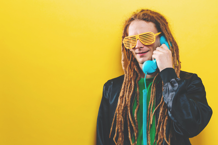 Dreadlocked man talking on old fashioned retro phone