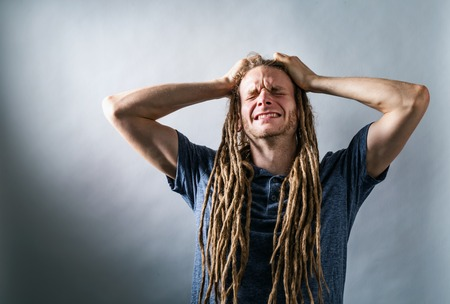 Young man feeling stressed out on a solid background Stock Photo