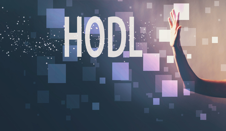 HODL with a hand in a dark light background