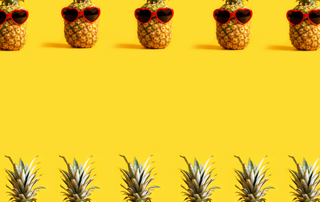 Series of pineapples wearing sunglasses on a yellow background