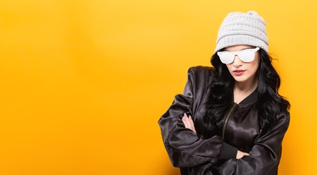 Fashionable woman with attitude in bomber jacket and sunglasses on a yellow background