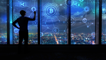 Cryptocurrency with man writing on large windows high above a sprawling city at night Zdjęcie Seryjne