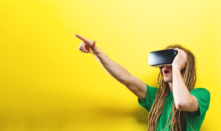 Young man using virtual reality headset on a solid background Stock Photo