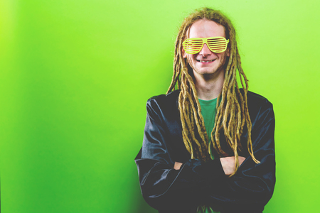 Funky fashion man with dreadlocks on a solid colored background Stock Photo