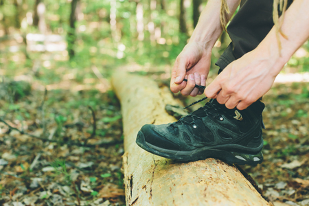 Hiker tying boot laces on a log in the forest Stok Fotoğraf