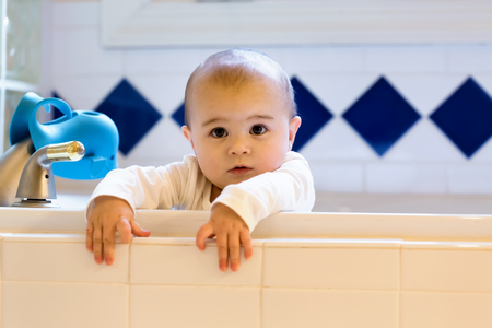 Toddler girl playing in the bathtub trying to climb out Banque d'images - 102569027