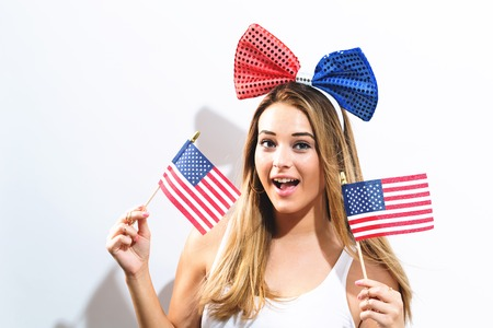 Happy young woman with American flags on the fourth of July 写真素材