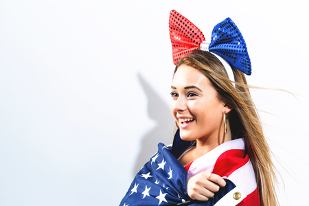 Happy young woman with an American flag on the fourth of July