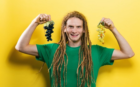 Happy man holding a green and purple grapes on a yellow background