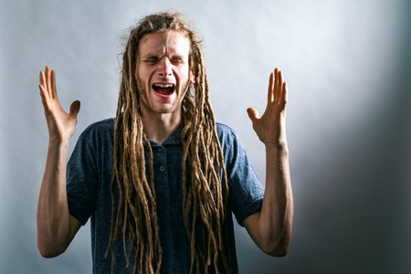 Young man screaming on a solid background Stock Photo