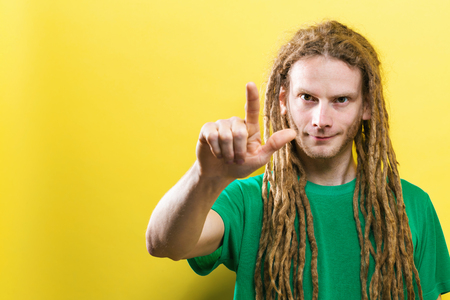 Young man pointing at something on a solid background Stock Photo